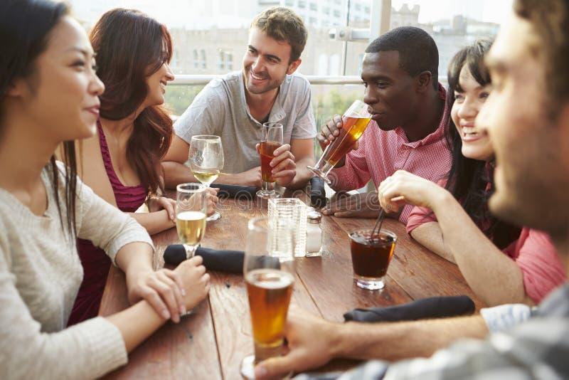 Grupp av vänner som tycker om drinken på den utomhus- takstången royaltyfria bilder