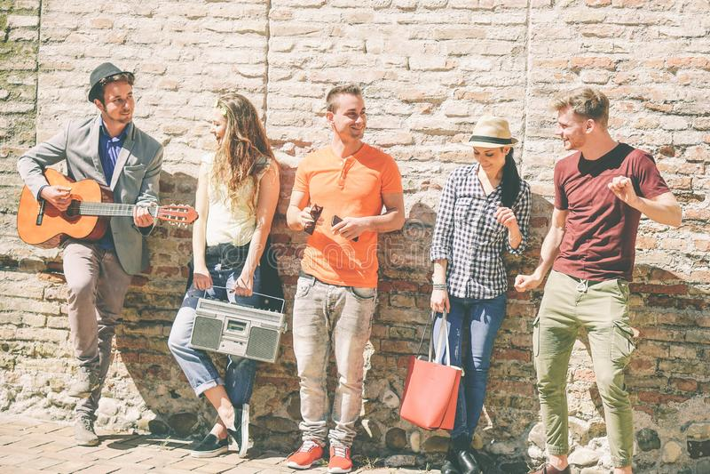 Grupp av vänner som tycker om en utomhus- spela gitarr för sommardag och en lyssnande musik med en tappningstereo royaltyfri fotografi