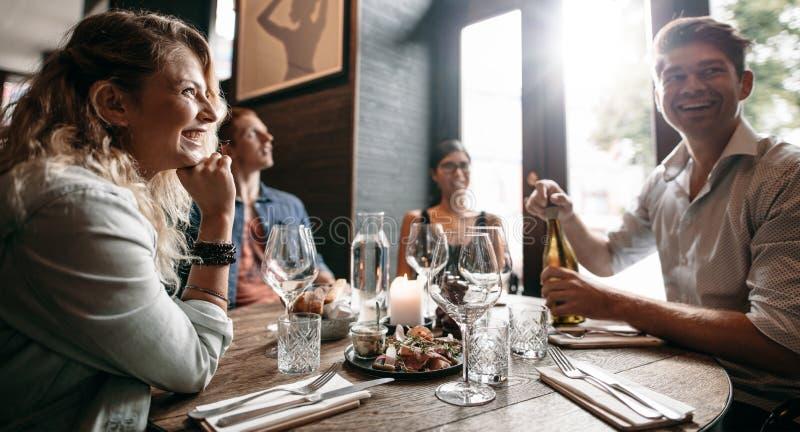 Grupp av vänner som tycker om ett aftonmål på en restaurang royaltyfri fotografi