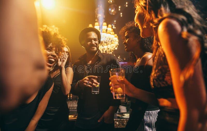 Grupp av vänner som tycker om ett parti på baren royaltyfri foto