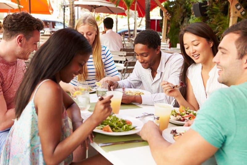 Grupp av vänner som tycker om lunch i utomhus- restaurang royaltyfri bild