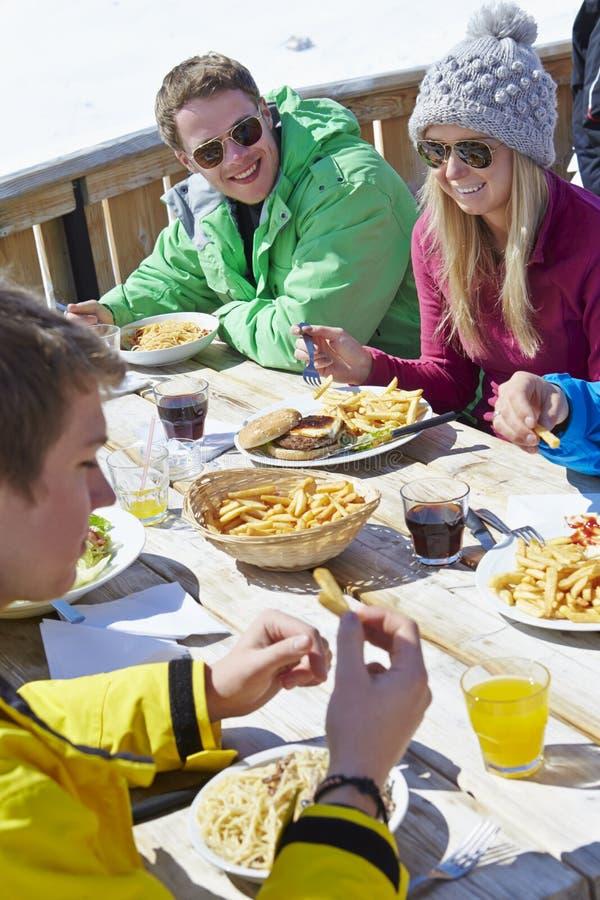 Grupp av vänner som tycker om mål i kafé på Ski Resort royaltyfri fotografi