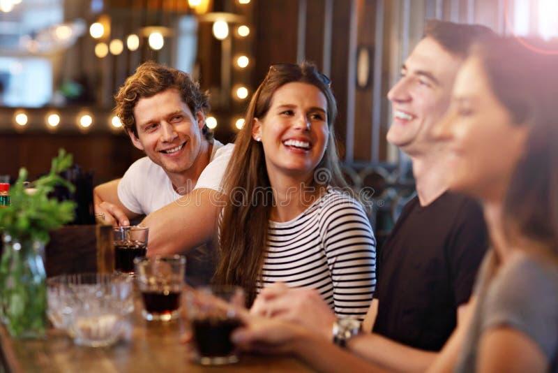 Grupp av vänner som tycker om mål i restaurang royaltyfri fotografi
