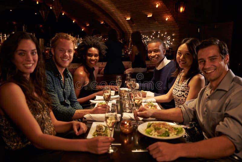 Grupp av vänner som tycker om mål i restaurang arkivfoto