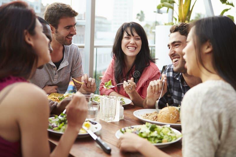 Grupp av vänner som tycker om mål på takrestaurangen arkivbild