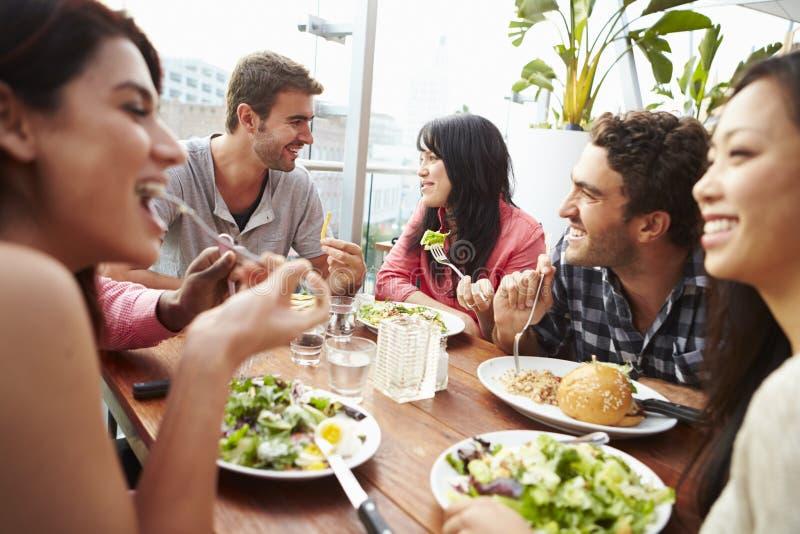 Grupp av vänner som tycker om mål på takrestaurangen arkivfoto