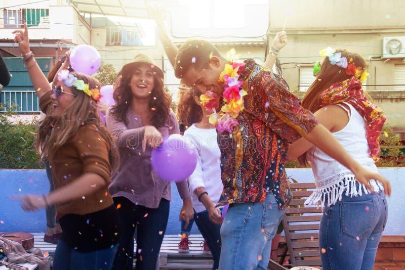 Grupp av vänner som tycker om på takpartiet och kastar konfettier fotografering för bildbyråer