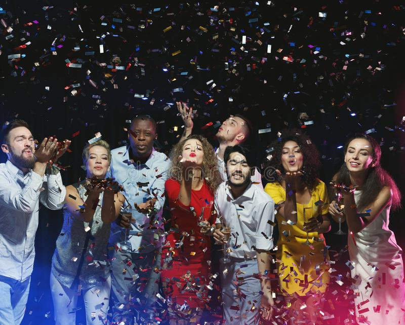 Grupp av vänner som tycker om partiet och blåser konfettier royaltyfri foto