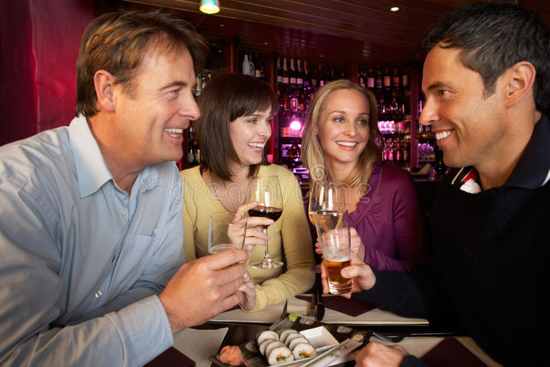 Grupp av vänner som tycker om Sushi i restaurang royaltyfria bilder