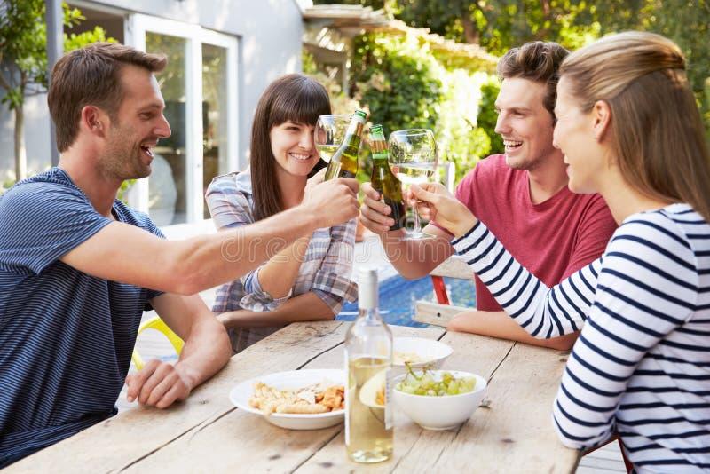 Grupp av vänner som tycker om utomhus- drinkar i trädgård royaltyfri fotografi