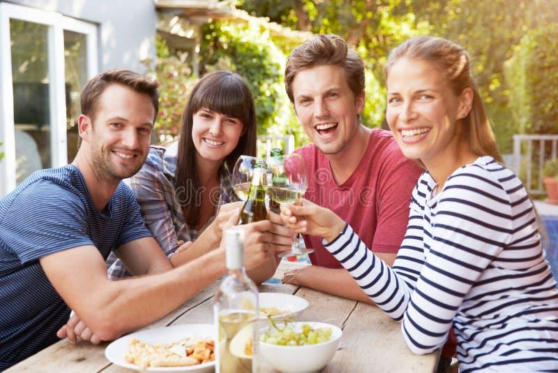 Grupp av vänner som tycker om utomhus- drinkar i trädgård arkivbilder