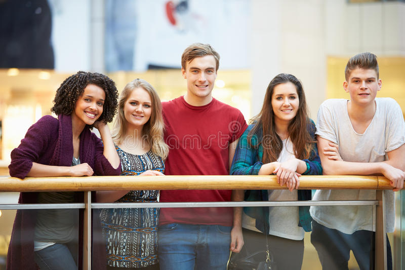 Grupp av vänner som ut hänger i shoppinggalleria royaltyfri foto