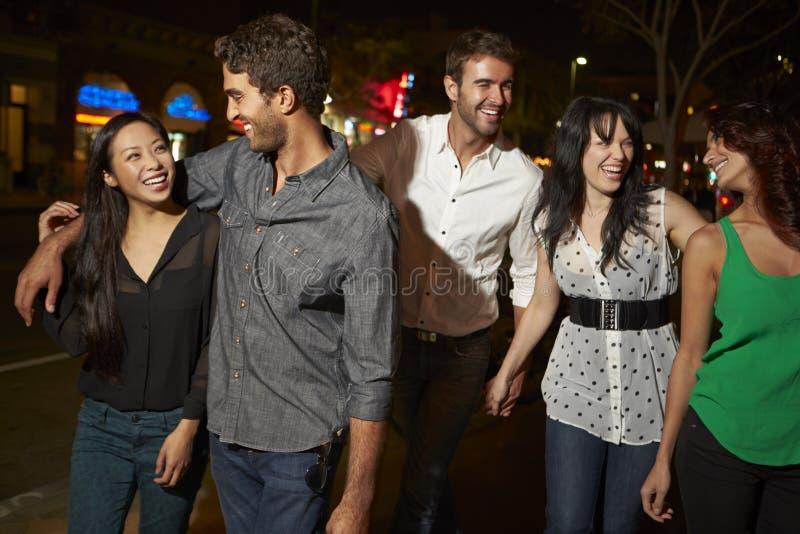 Grupp av vänner som ut tycker om natt tillsammans arkivfoto