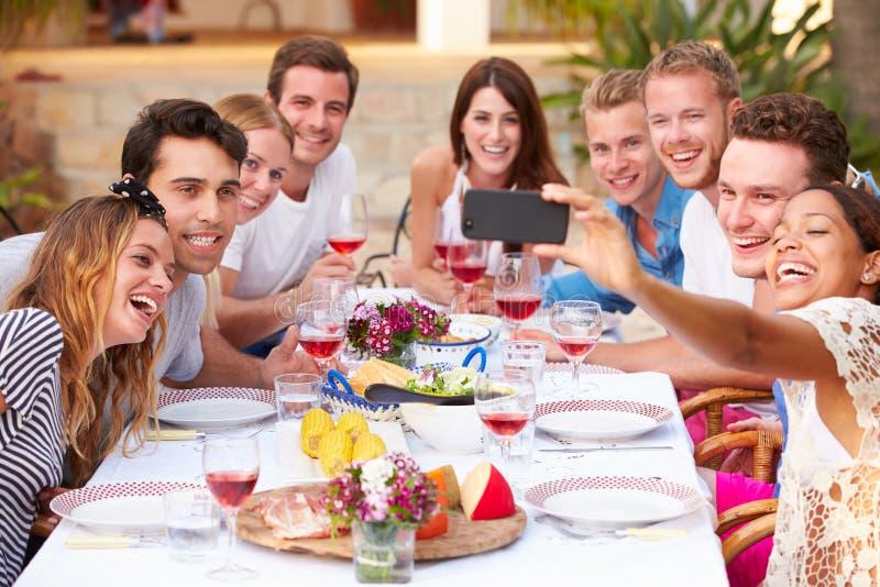 Grupp av vänner som utomhus tar Selfie under lunch arkivfoton