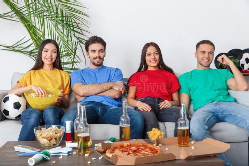 Grupp av vänsportfans som håller ögonen på matchen i kopplade av färgrika skjortor arkivfoto