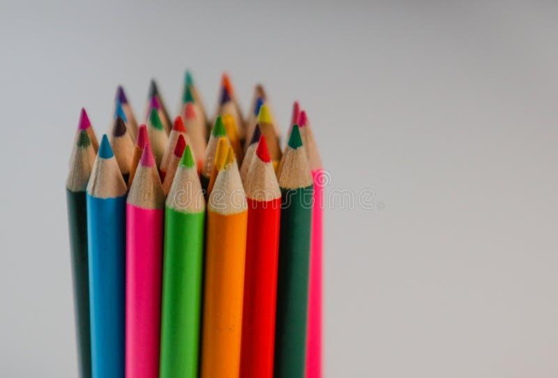Grupp av vässade kulöra blyertspennor som grupperas i cirkeln arkivfoton