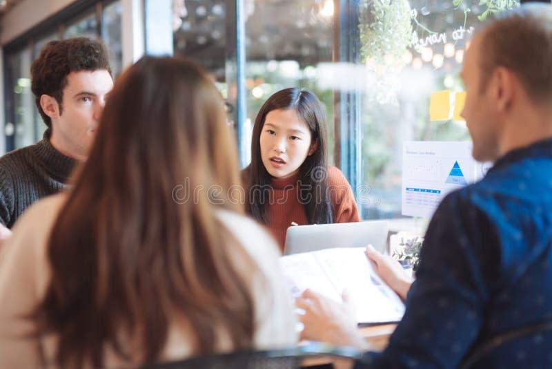 Grupp av v?nner som pratar och anv?nder b?rbara datorn i kaf? p? coffee shopkaf?t i universitet som tillsammans talar och skratta royaltyfri bild