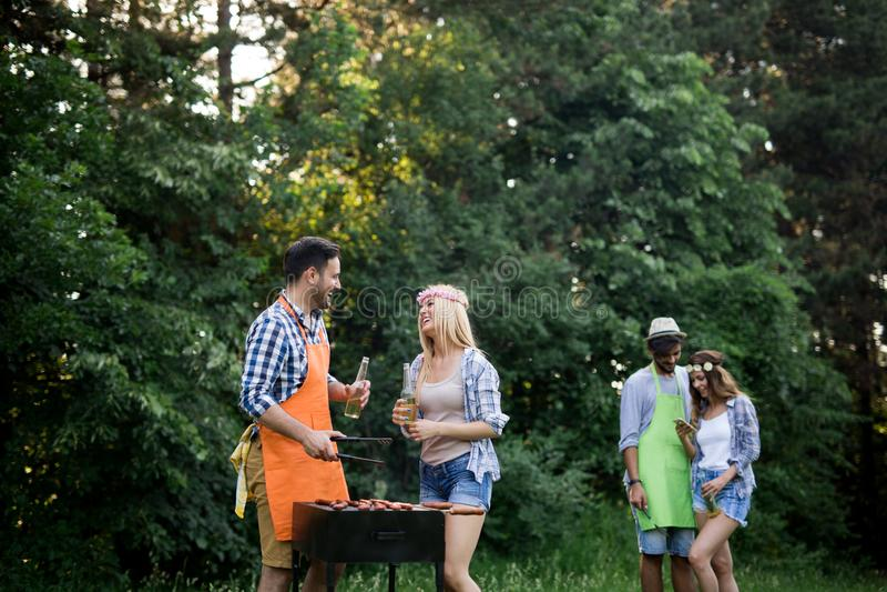 Grupp av v?nner som tillsammans g?r en grillfest utomhus i naturen royaltyfri foto
