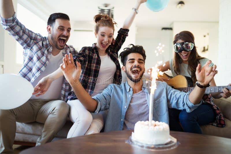 Grupp av v?nner som tycker om och firar f?delsedag och att festa arkivbilder
