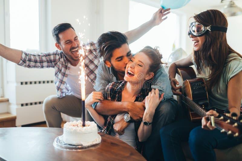 Grupp av v?nner som tycker om och firar f?delsedag och att festa royaltyfri fotografi
