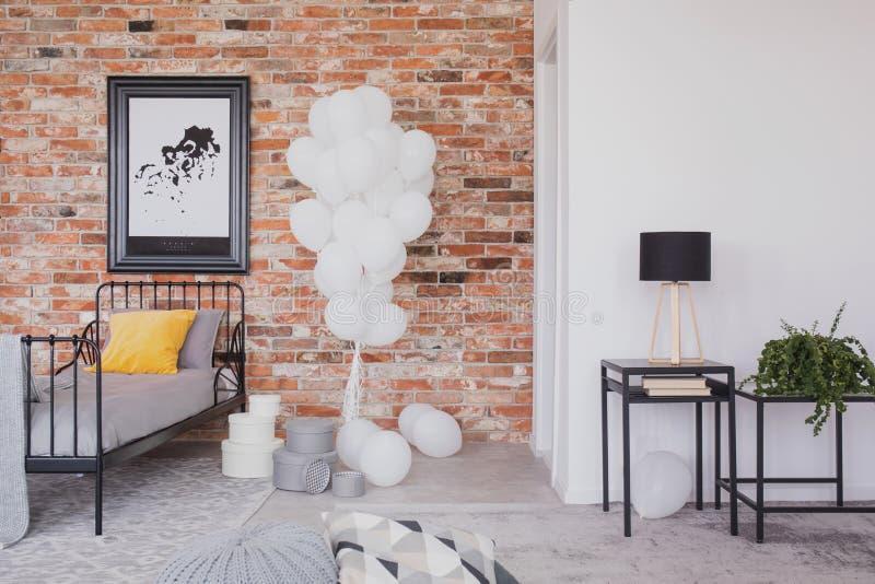 Grupp av vita ballonger bredvid enkel svart metallsäng med grå sängkläder och den gula kudden i det industriella sovrummet som är arkivfoto