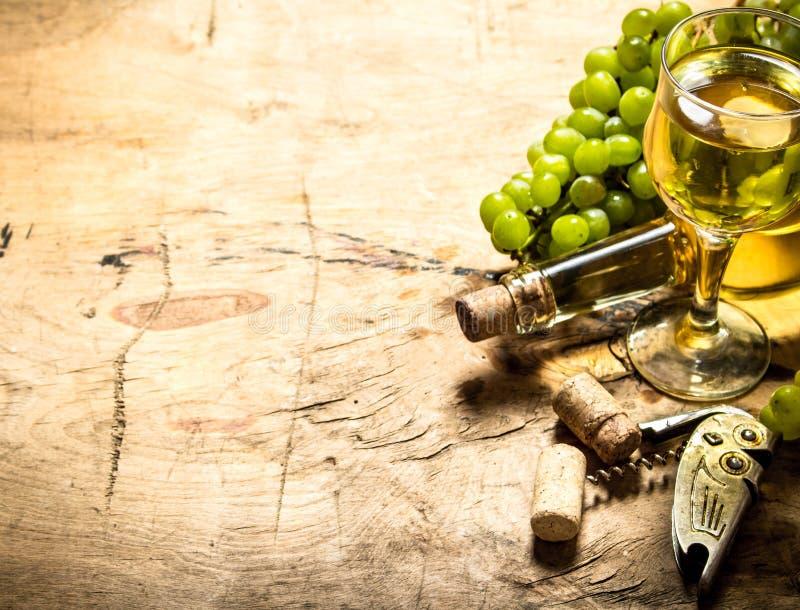 Grupp av vita druvor med vin, en korkskruv och proppar arkivbild