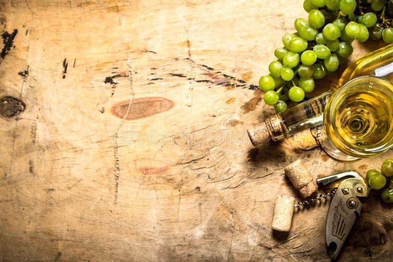 Grupp av vita druvor med vin, en korkskruv och proppar arkivbilder