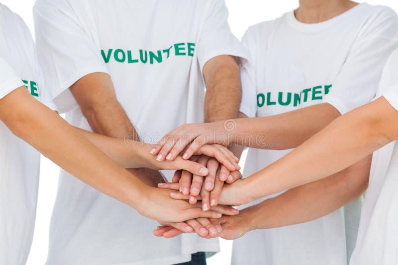 Grupp av volontärer som tillsammans sätter händer arkivbild
