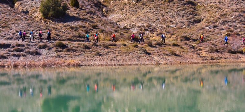 grupp av vuxet folk med den färgrika ryggsäcken som trekking på en bana av sand och stenar som går bredvid en sjö som reflekterar arkivfoton