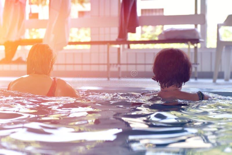 Grupp eller ungt och högt folk i aquarobic öva för konditionsimbassäng fotografering för bildbyråer