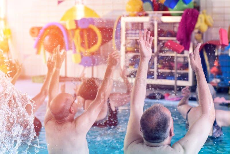Grupp eller ungt och högt folk i aquarobic öva för konditionsimbassäng royaltyfri foto