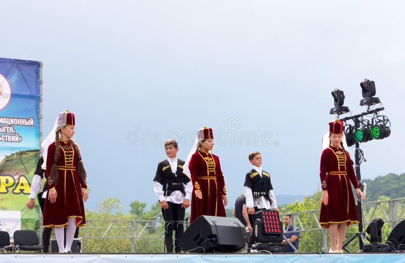 Grupp för dans för barn` s i traditionell Circassiankläder på den öppna Adyghe ostfestivalen arkivfoton