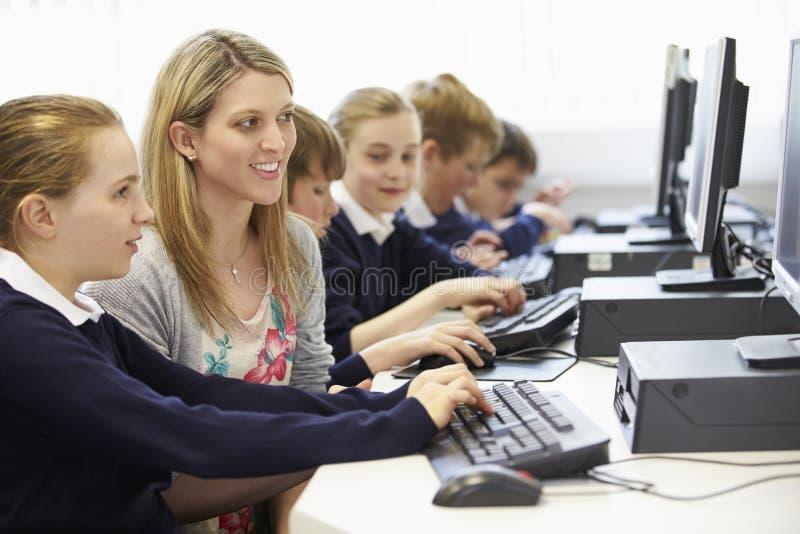 Grupp för dator för lärareAnd Pupil In skola arkivfoto