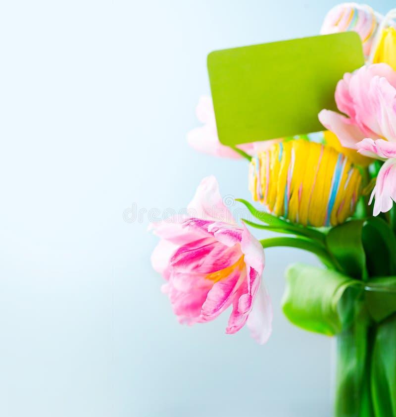 Grupp för påskferieblommor med hälsningkortet arkivfoto