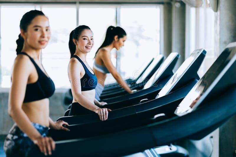 Grupp för sidosikt av sunda attraktiva sportkvinnor på körande spår Sunt sportar, livsstil, konditionidrottshallbegrepp arkivfoton