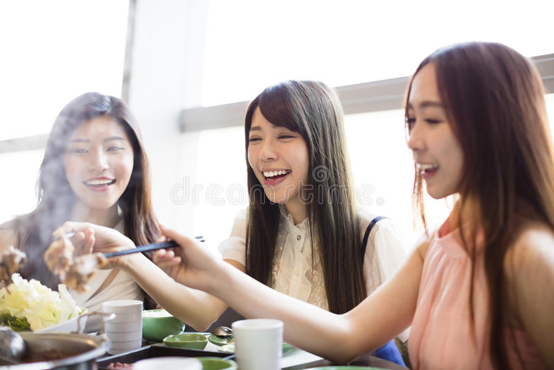 Grupp för unga kvinnor som äter den varma krukan arkivfoton
