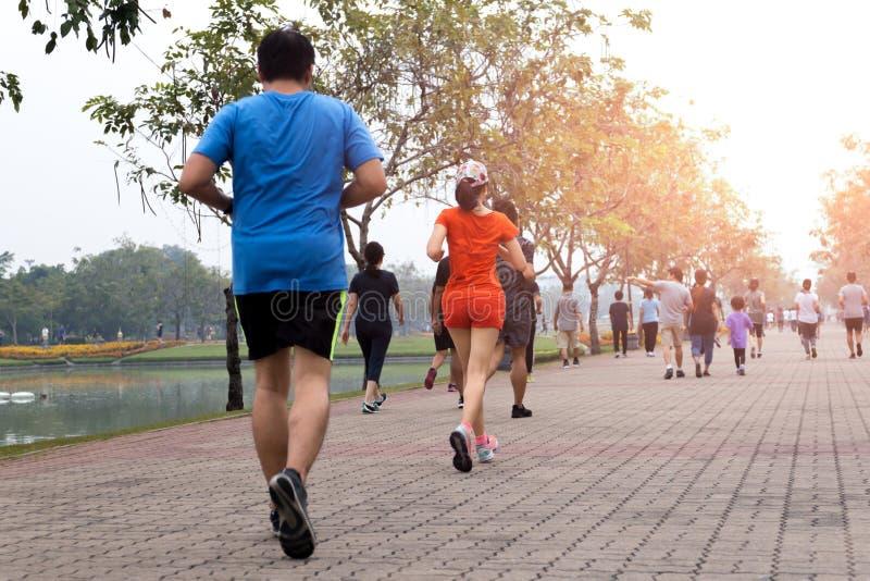 Grupp människorövning som går och joggar i parkera royaltyfri bild