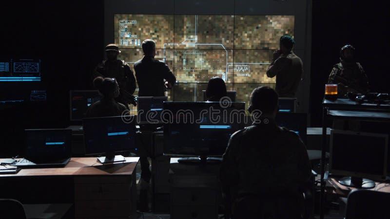 Grupp människor i mörkt rum som lanserar en missil arkivbild