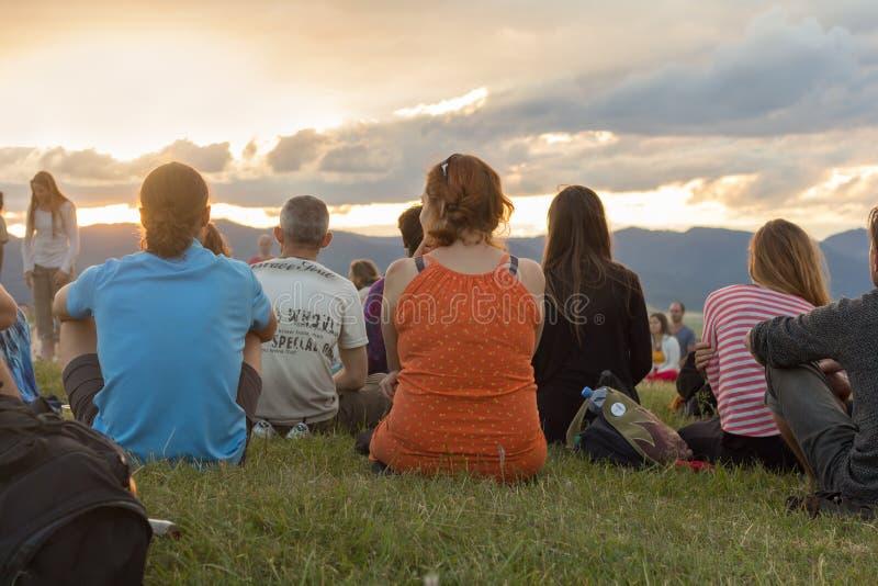 Grupp människor i natur som tycker om solnedgång arkivbild