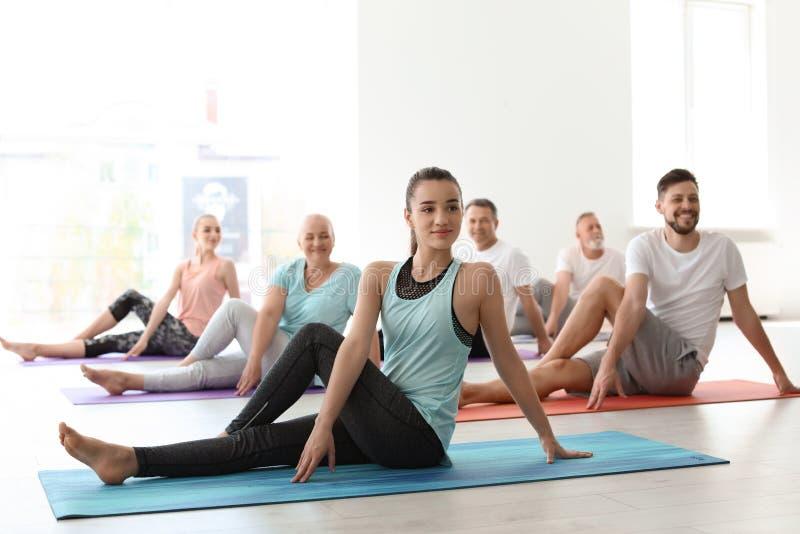 Grupp människor i praktiserande yoga för sportswear arkivbilder