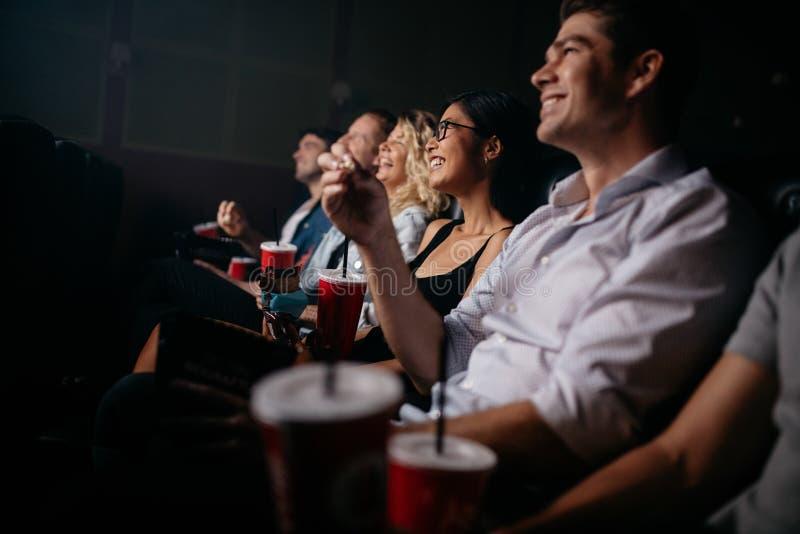Grupp människor i teater med popcorn och drinkar royaltyfri fotografi