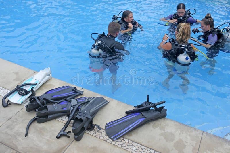 Grupp människor lär dyker med dykarutrustning i en pöl i den Rarotonga kocken arkivbilder