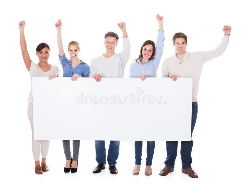 Grupp människor med affischtavlan som lyfter handen arkivbild