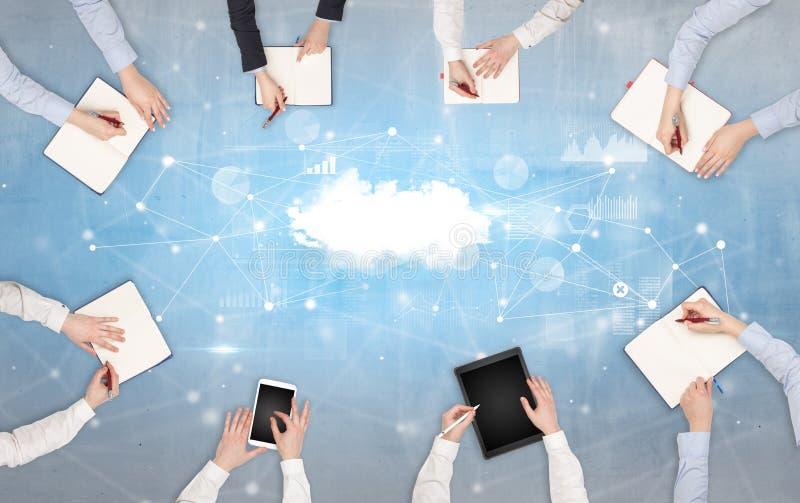 Grupp människor med apparater i händer som arbetar på bärbara datorer och minnestavlor med online-teamworkbegrepp arkivbild