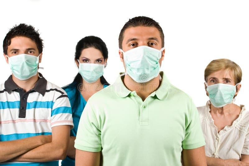 Grupp människor med den skyddande maskeringen arkivfoton