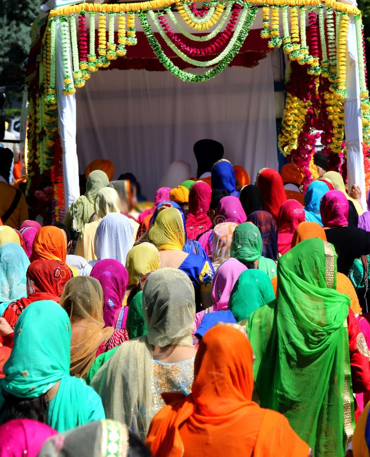 grupp människor med färgrik kläder och kvinnor med skyler i royaltyfria foton