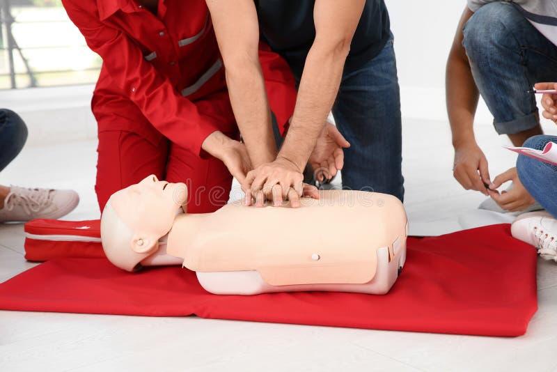 Grupp människor med instruktören som först öva CPR på hjälpmedelgrupp för skyltdocka inomhus arkivbilder