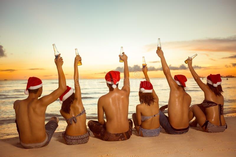 Grupp människor med jultomtenhattar som sitter på den sandiga stranden royaltyfri bild