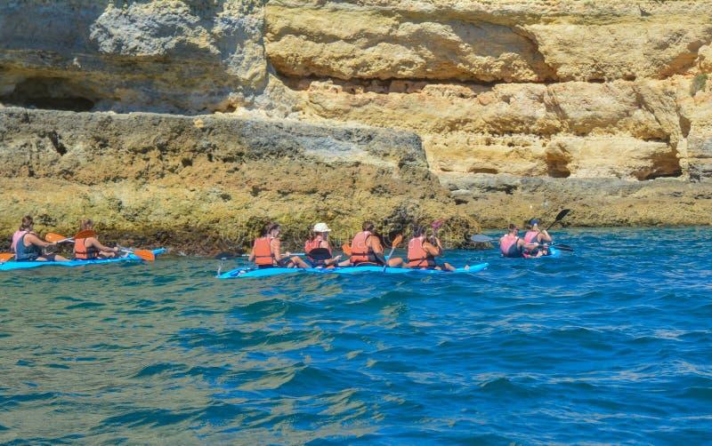 Grupp människor på att kanota i havet med berg kajaker arkivfoton