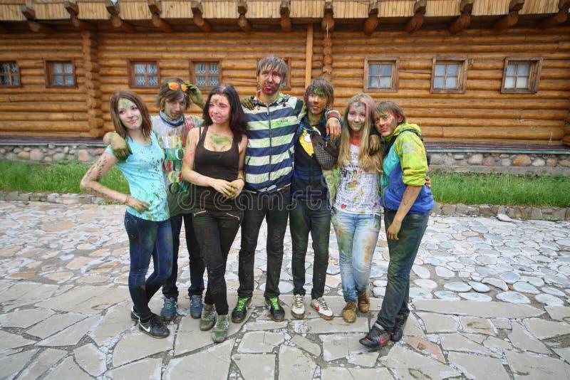 Grupp människor på en bakgrund av träbyggnad arkivfoto